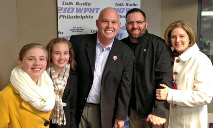 Chris Stigall, left of Sergeant First Class Keaton, surrounded by the Keaton family in the 1210 WPHT studio